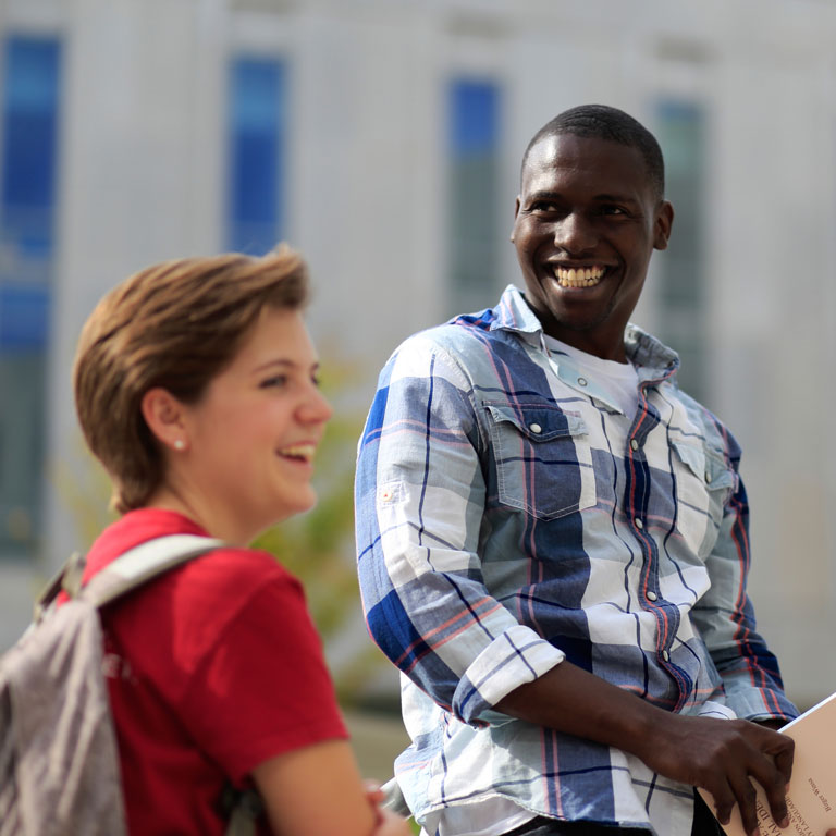 Male and female student smiling, laughing