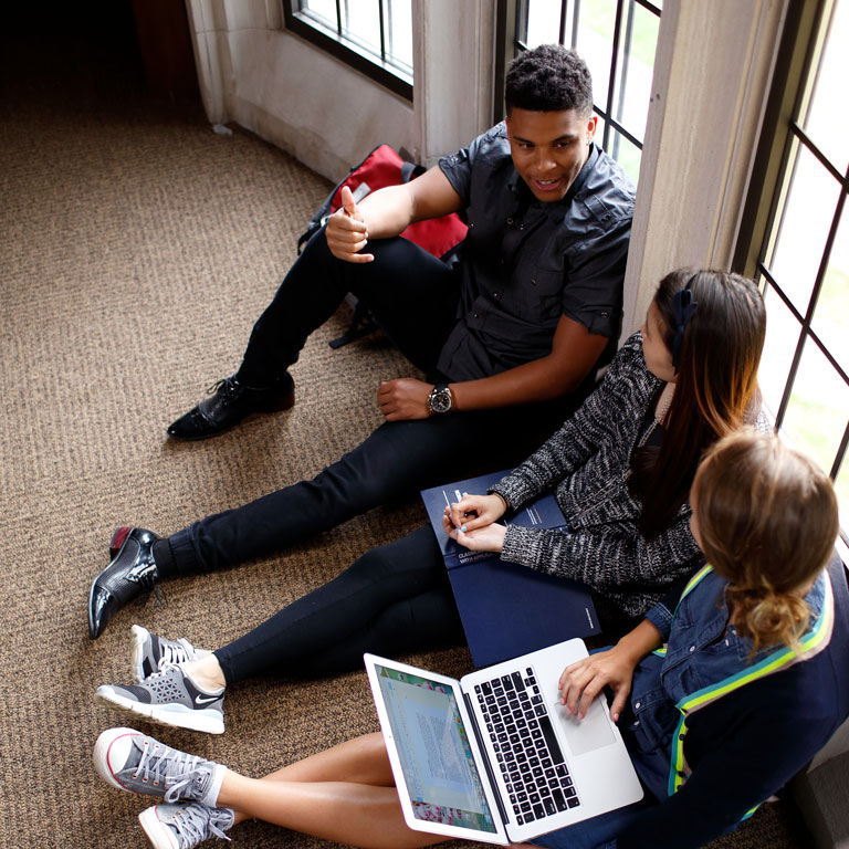 Students sitting on the floor with laptop having a conversation.
