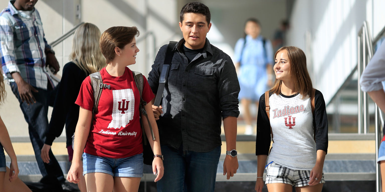 Three students walking hall steps speak with each other.